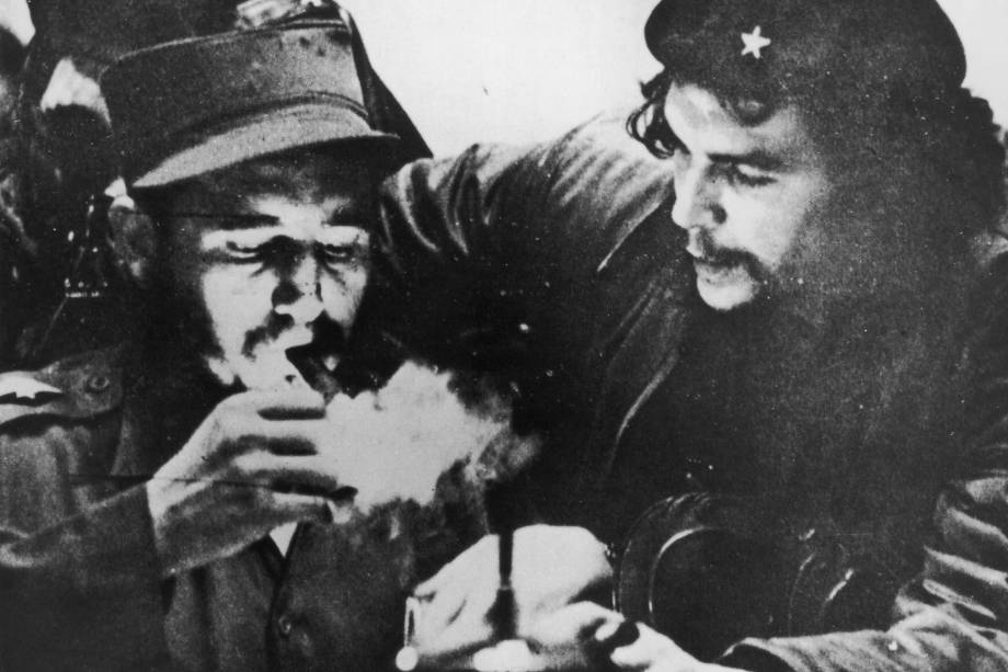 Fidel Castro acende seu charuto ao lado do argentino Che Guevara (1928-1967) durante os primeiros dias de sua campanha de guerrilha nas montanhas Sierra Maestra em Cuba, por volta de 1956