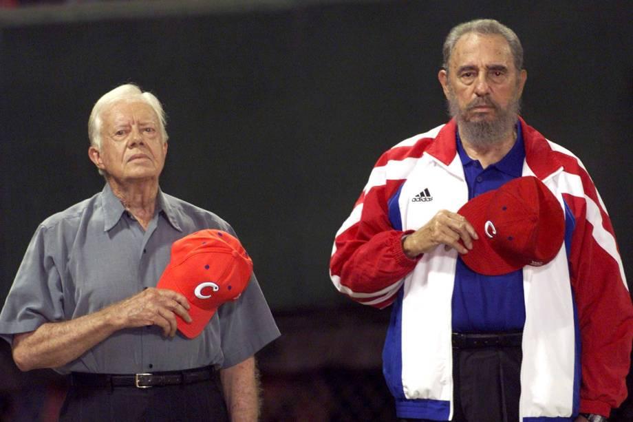 """O ex-presidente norte-americano Jimmy Carter e o então ditador cubano Fidel Castro ouvem o hino nacional cubano no estádio de beisebol """"Latinoamericano"""" em Havana em maio de 2002"""