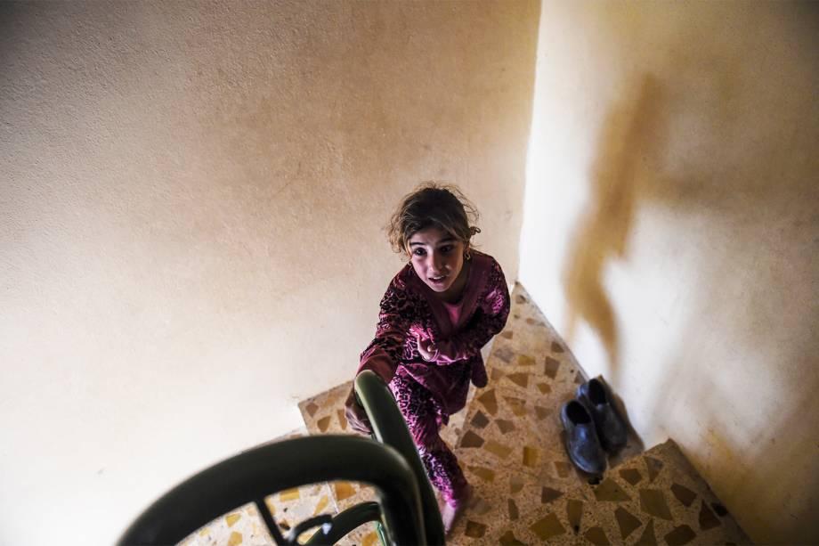 Garota iraquiana é vista na escadaria de uma mesquita onde civis estão se refugiando na vila de Gogjali, em Mosul - 02/11/2016
