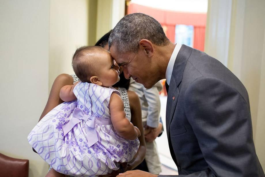 Presidente Barack Obama cumprimenta a filha de Tim Gronniger, Josephine Gronniger, durante foto em família no Salão Oval da Casa Branca - 17/07/2015