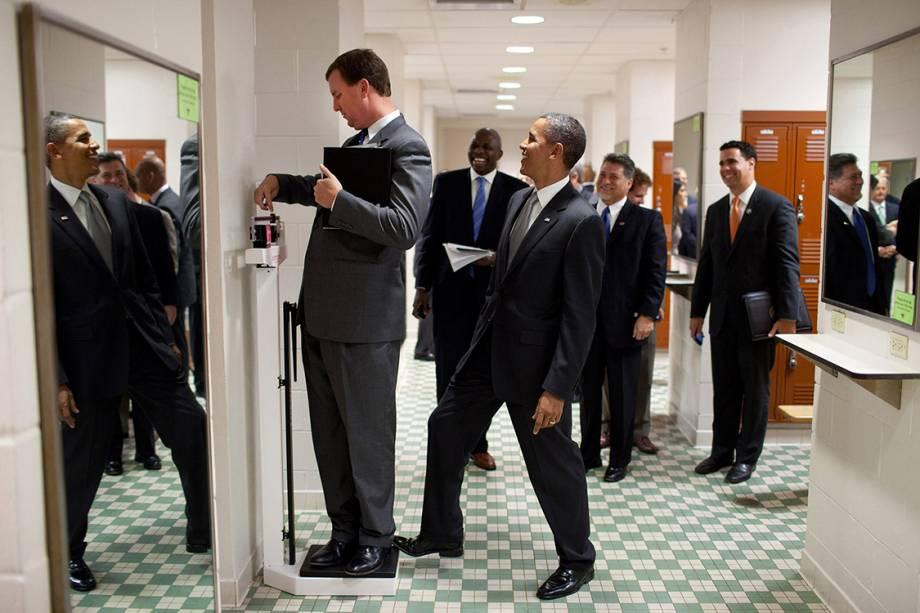 Obama coloca pé em balança enquanto diretor Marvin Nicholson mede seu peso em um vestiário durante visita à Universidade do Texas - 09/08/2010