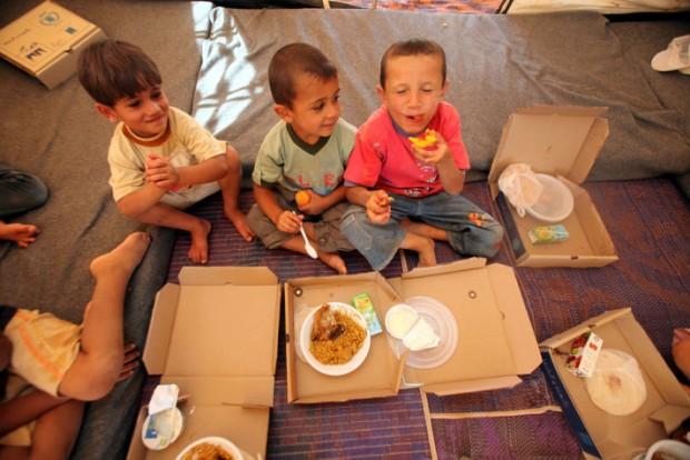 Garotos sírios recebem alimentos da ONU em acampamento na Jordânia (Foto Anadolu Ajansi/ Salah Malkawi/ ONU Divulgação)