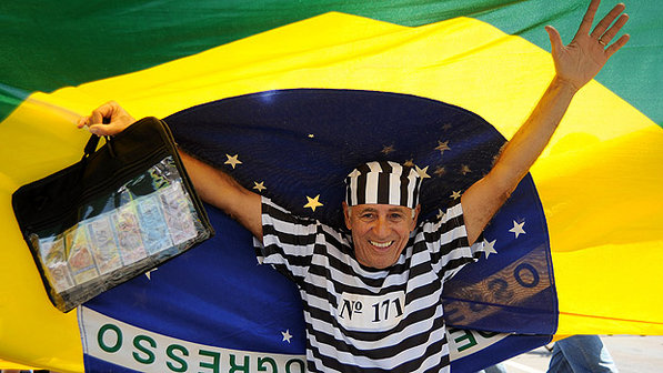 Um dos manifestantes de Brasília: com roupa de presidiário e mala de dinheiro (Foto:Pedro Ladeira/AFP)