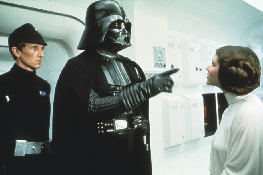 "David Prowse, como Darth Vader, e Carrie Fisher no filme ""Star Wars: Episósio IV - Uma Nova Esperança"", de George Lucas."