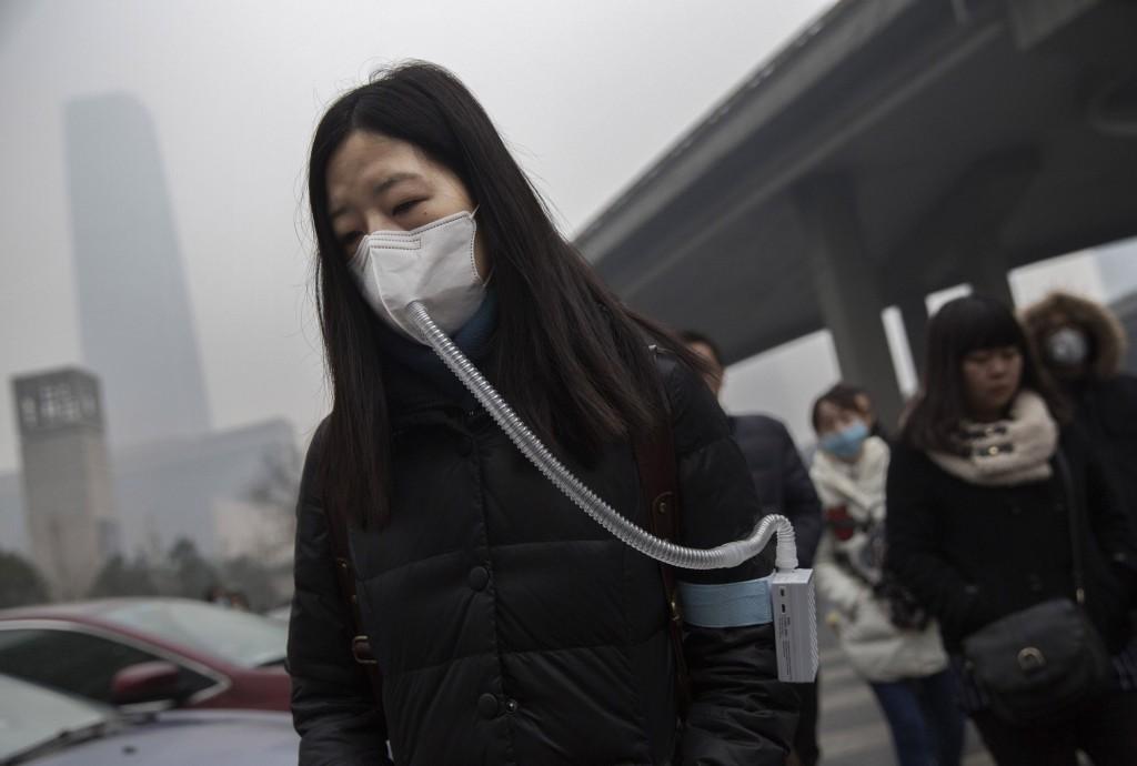 Mulher com máscara contra poluição em Pequim, na China. A cidade decretou alerta vermelho no início de dezembro, pela primeira vez. Crédito Kevin Frayer/Getty Images