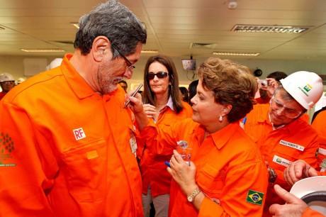 Dilma Rousseff autografa o macacão do ex-presidente da Petrobras, José Sérgio Gabrielli. Ao fundo, é observada por Graça Foster, também investigada pela compra de Pasadena e Paulo Roberto Costa, delator do esquema de corrupção na estatal