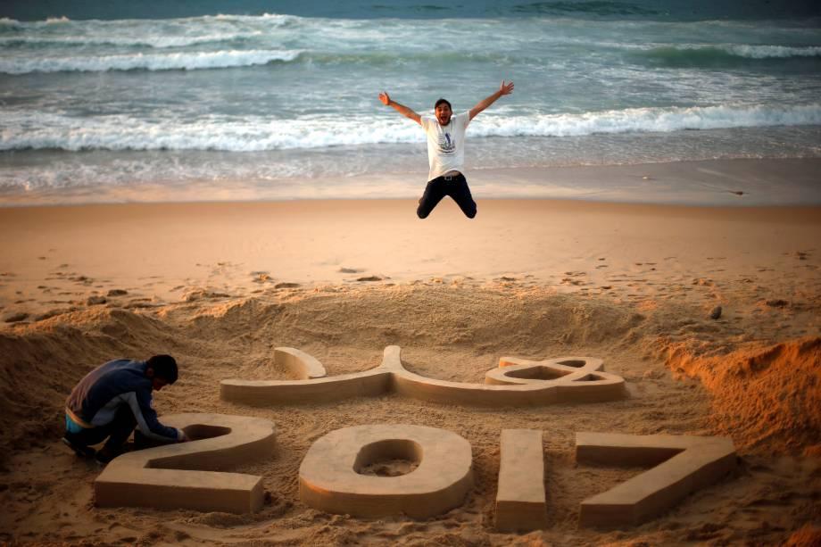 """Artista palestino Yazed Abu Jarad faz os últimos retoques em uma escultura de areia que diz """"Bem-vindo 2017"""", em uma praia no norte da Faixa de Gaza"""