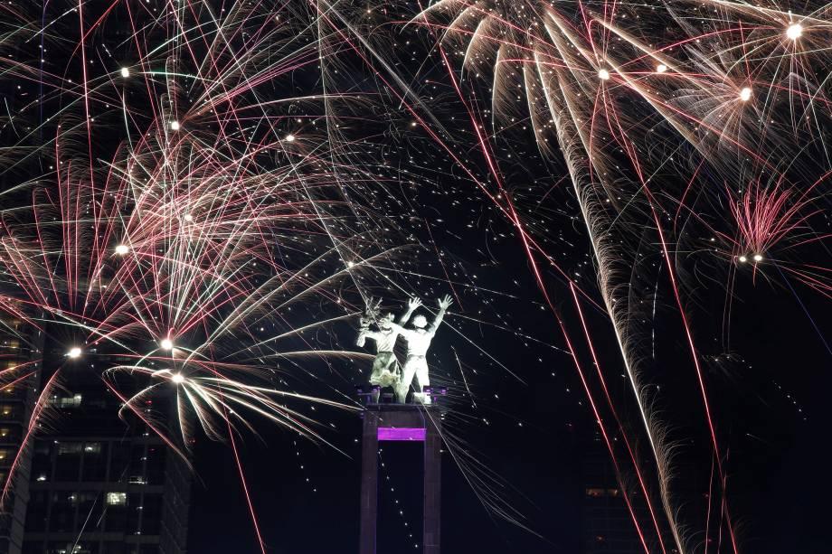 Fogos de artifício explodem em torno do monumento de Selamat Datang durante celebrações de Ano Novo em Jakarta, na Indonésia