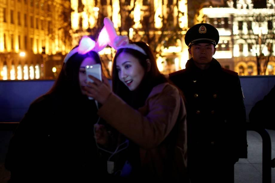 Mulheres tiram uma selfie ao lado de um oficial de polícia enquanto participam nas celebrações de Ano Novo, em Xangai na China
