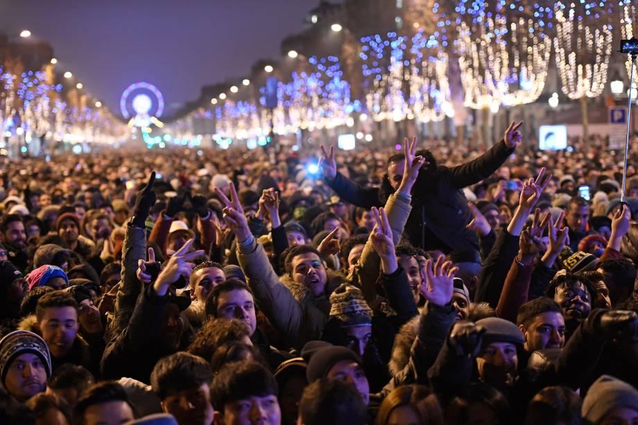 Público se reúne na avenida Champs-Elysees para assistir a um show de mapeamento de laser e vídeo 3D sobre o tema da candidatura de Paris para os Jogos Olímpicos de 2024, projetado no Arco do Triunfo como parte das comemorações de Ano Novo em Paris