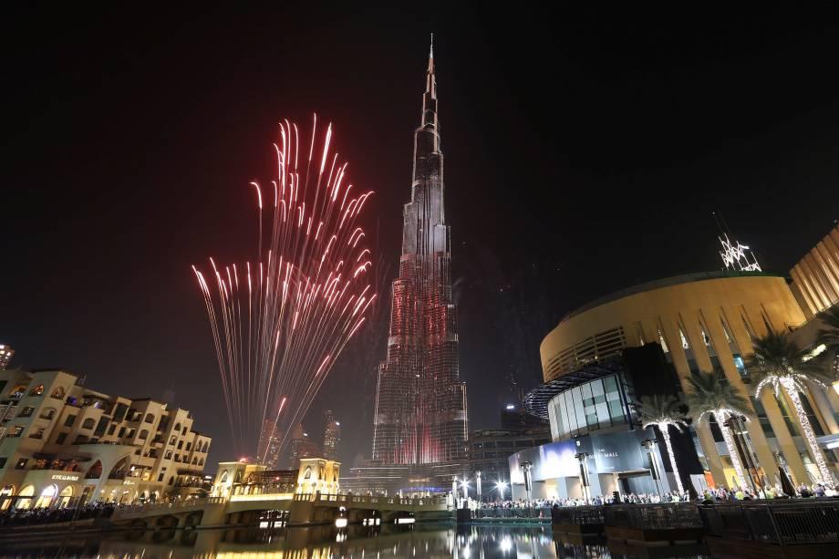 Fogos de artifício explodem ao redor no edifício o mais alto do mundo, Burj Khalifa, em Dubai durante as celebrações do Ano Novo