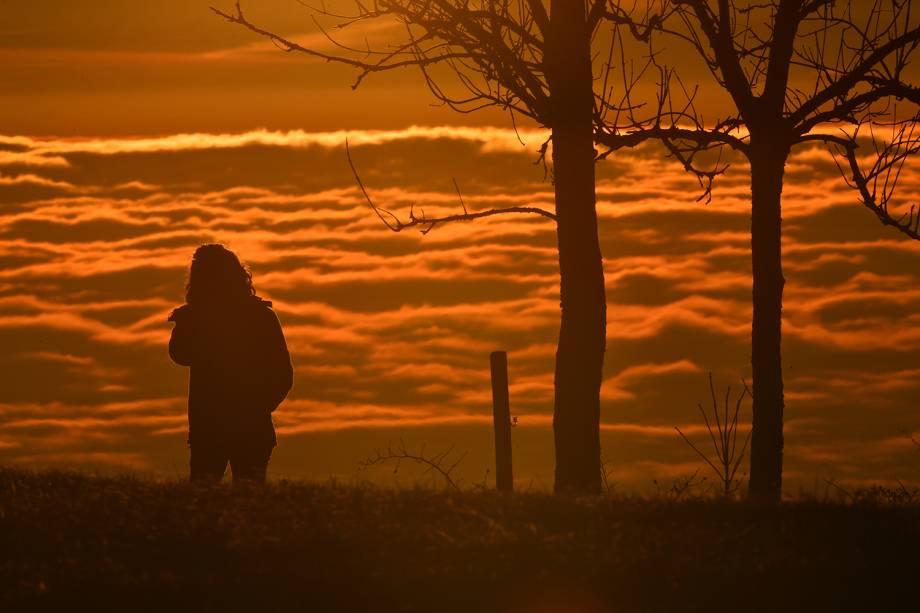 Mulher observa nascer do sol por detrás de nuvens em no monte Hoechsten, sul da Alemanha - 08/12/2016