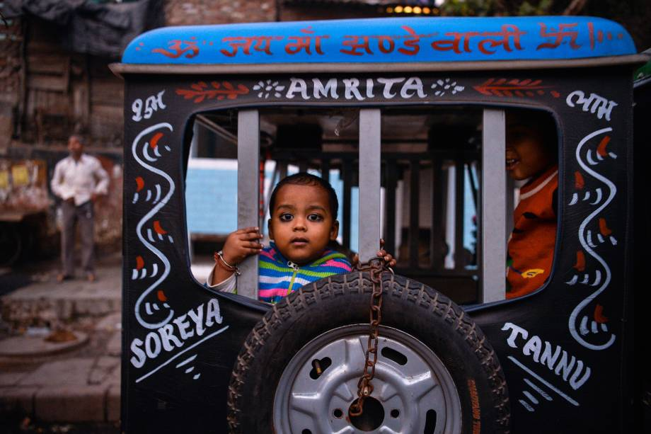 Criança indiana olha por detrás de uma carroça durante festival em Nova Délhi, na Índia - 01/12/2016