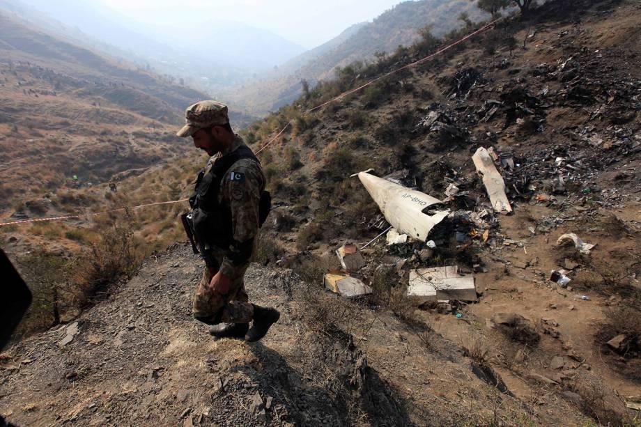 Soldado paquistanês patrulha a área onde caiu um avião da Pakistan International Airline, próximo à região de Abbotabad, no Paquistão - 08/12/2016