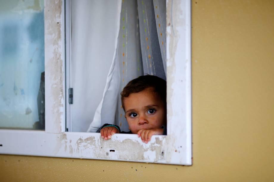 Garoto refugiado sírio olha por uma janela no acampamento de Elbeyli, em Kilis, próximo a fronteira entre Síria e Turquia - 01/12/2016