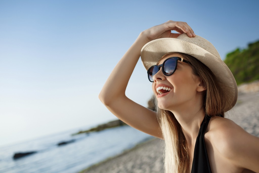 Beautiful young  cheerful girl wearing glasses rest on beach at morning