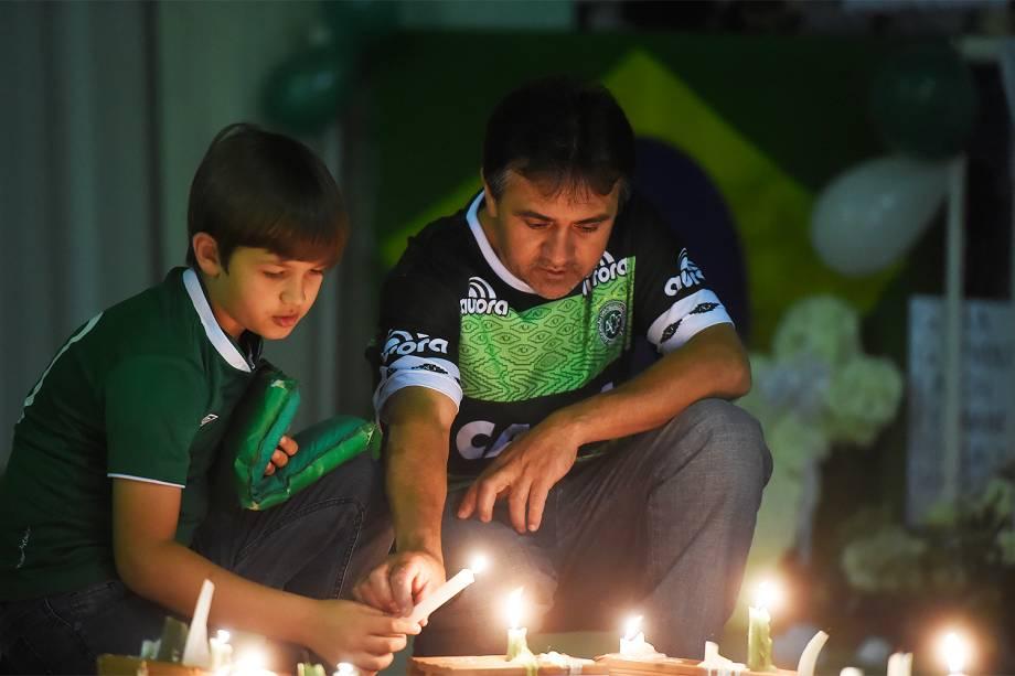 Pai e filho acendem velas em homenagem às vítimas do acidente de avião da Chapecoense