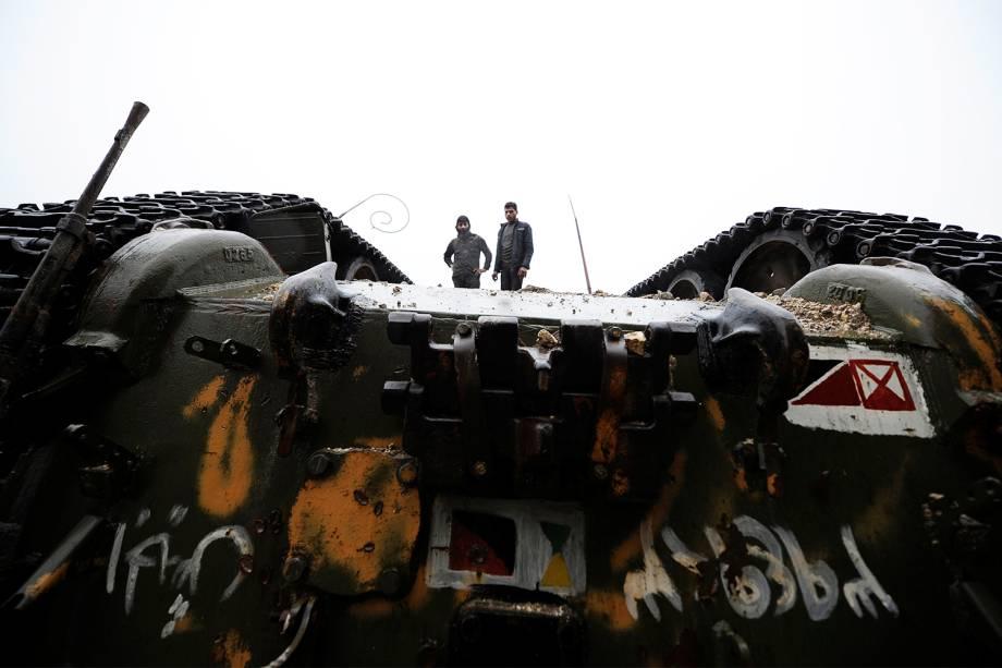 Membros de forças governamentais do ditador sírio Bashar Assad observam tanque de guerra virado em Alepo - 15/12/2016