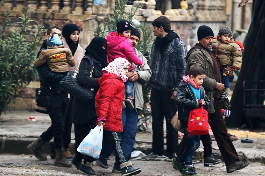 Pessoas carregam pertences ao serem retiradas de áreas rebeldes de Alepo, na Síria - 13/12/2016