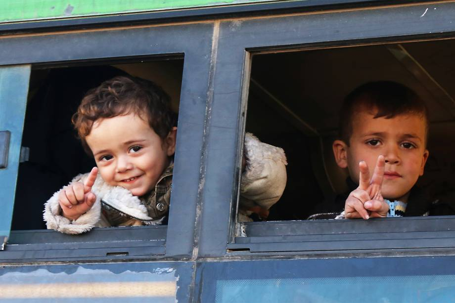 Crianças sírias são fotografadas em ônibus ao serem evacuadas da região de Khan al-Aassal, no oeste de Alepo - 15/12/2016
