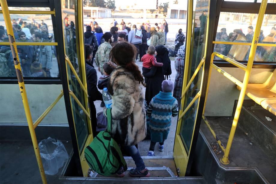 Sírios entram em ônibus para ser evacuados da região de Khan al-Aassal, oeste de Alepo - 15/12/2016