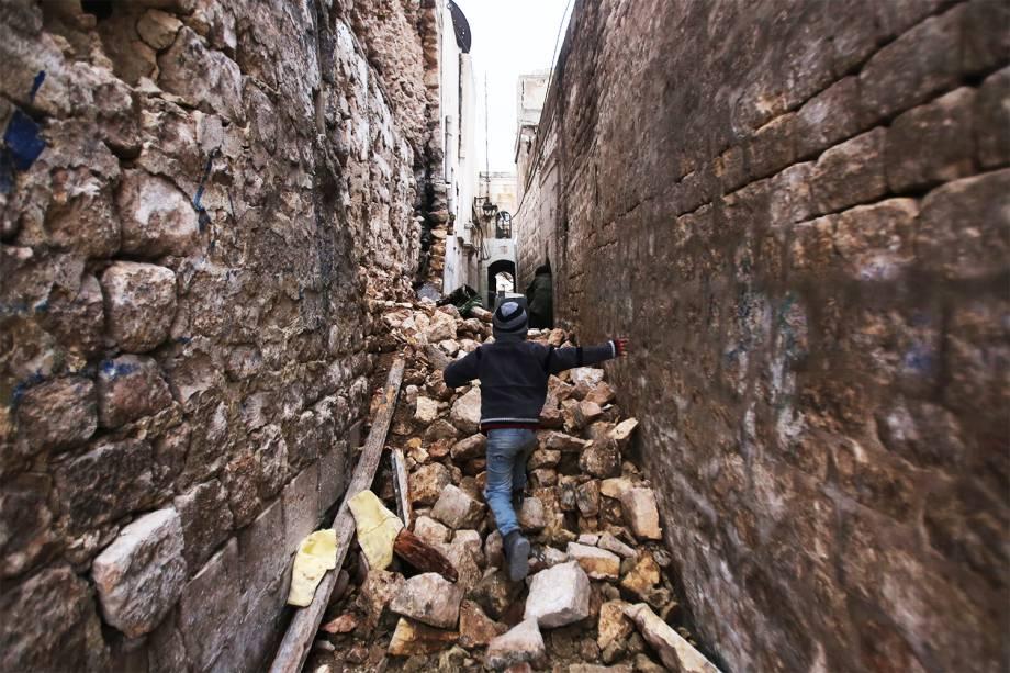 Garoto sírio caminha entre prédios destruídos, no bairro de Dahret Awad, em Alepo, durante a evacuação de áreas rebeldes do local - 17/12/2016