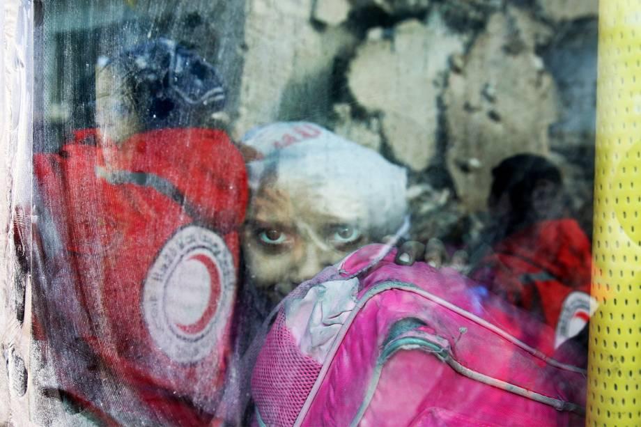 Garota é vista dentro de ônibus, durante evacuação de moradores no leste de Alepo, na Síria - 18/12/2016
