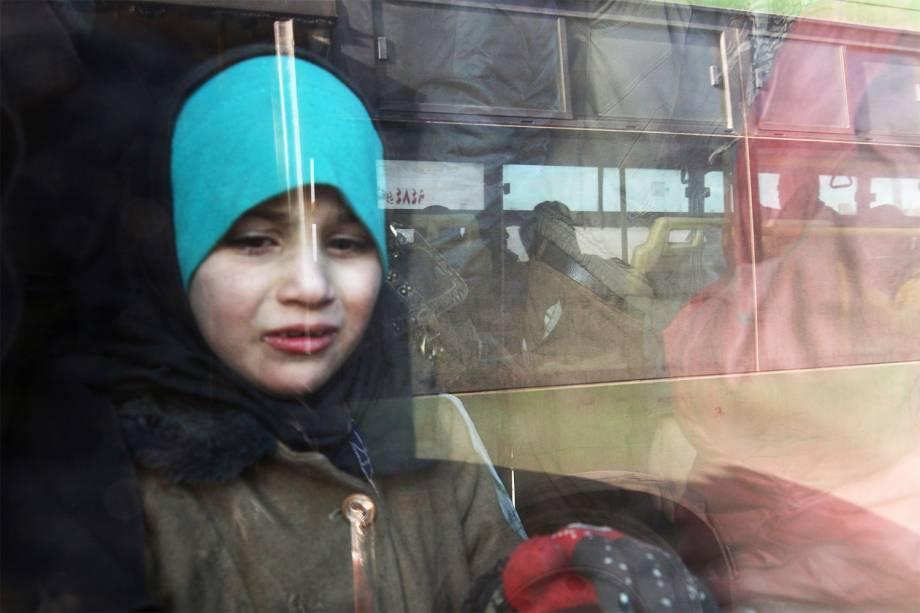 Garota é vista em ônibus durante evacuação de moradores de área rebelde no leste de Alepo - 18/12/2016