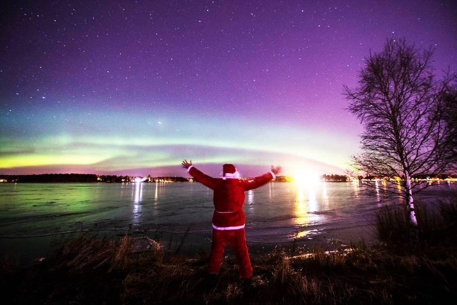 Um homem vestido de Papai Noel observa a<em>aurora boreal</em> em Vaasa, na Finlândia - 24/12/2016