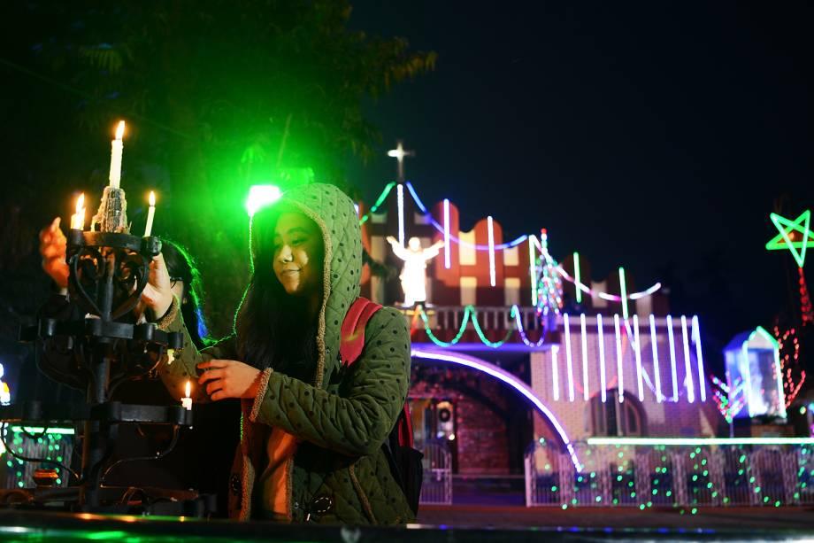 Jovem indiana acende velas perto da igreja iluminada da rainha de nossa senhora na véspera de Natal em Siliguri dezembro - 24/12/2016