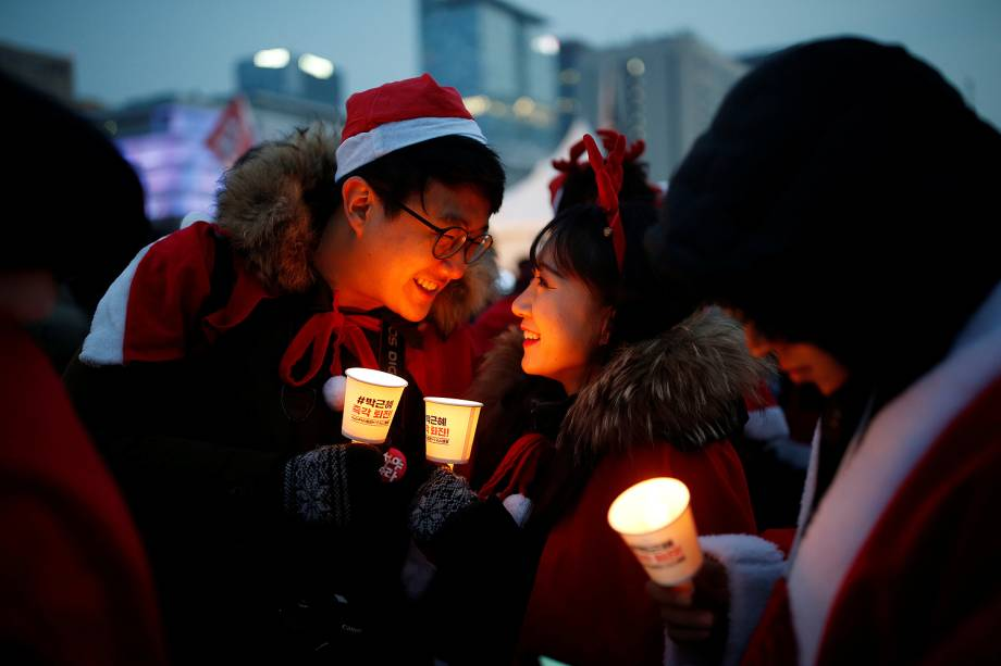 Casal com com trajes natalinos durante protesto que pede a renúncia da presidente sul-coreana Park Geun-hye, em Seul - 24/12/2016