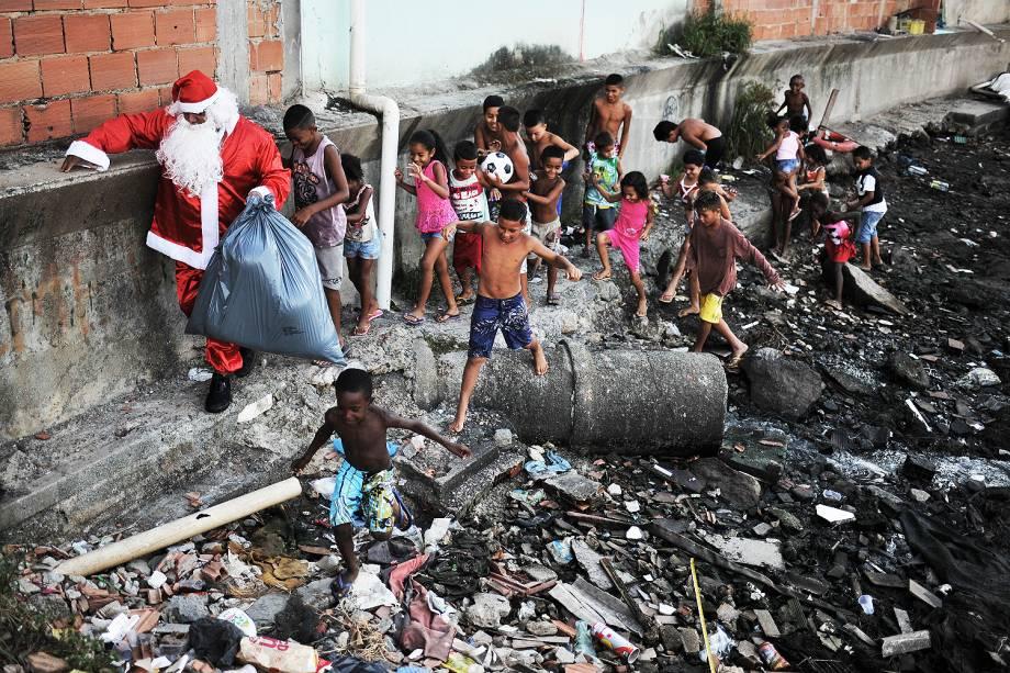 Homem vestido de Papai Noel visita a favela da Maré, na zona norte do Rio de Janeiro - 24/12/2016