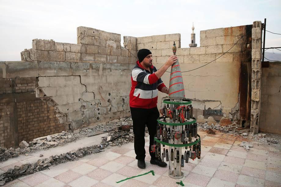Um homem monta uma árvore de Natal decorada com projéteis vazios que ele recolheu e pintou na cidade controlada por rebeldes de Douma, na Síria - 25/12/2016