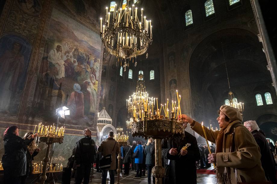 Uma mulher acende velas durante uma missa de Natal na catedral Alexander Nevsky em Sófia, na Bulgária