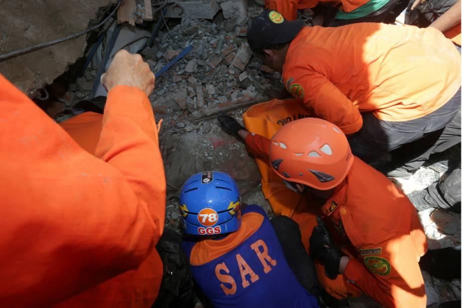 Socorristas tentam resgatar pessoas soterradas após o terremoto na Indonésia