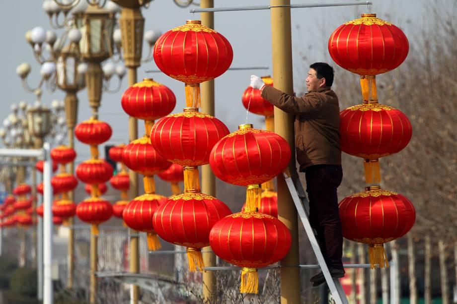 Homem pendura lanternas    em postes para comemorar o ano novo chinês no calendário lunar, na China