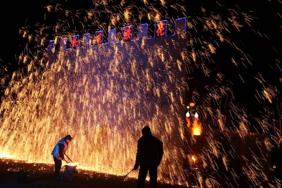 Homens atiram ferro derretido em uma parede durante as festividades do ano novo chinês, na China