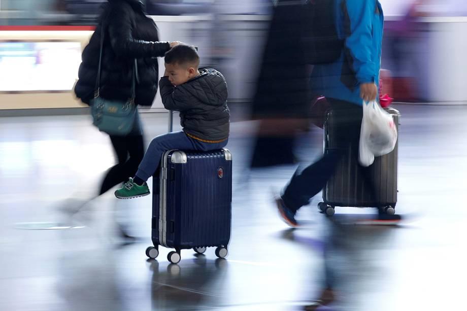 Menino descansa sobre uma mala em uma estação de trem. Milhares de chineses viajaram para celebrar o ano novo chinês, na China