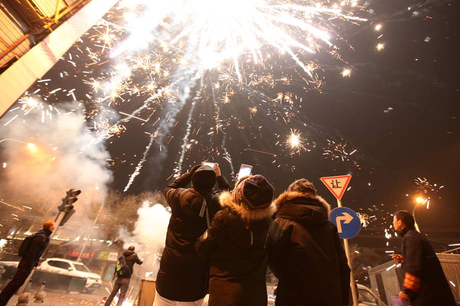 Pessoas assistem à exibição de fogos de artifício durante as festividades do ano novo chinês, na China