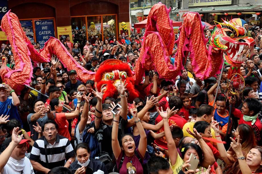 Pessoas tentam pegar os envelopes vermelhos que contêm o dinheiro na frente de um estabelecimento de negócio em comemoração do ano novo chinês em Manila, Filipinas - 28/01/2017
