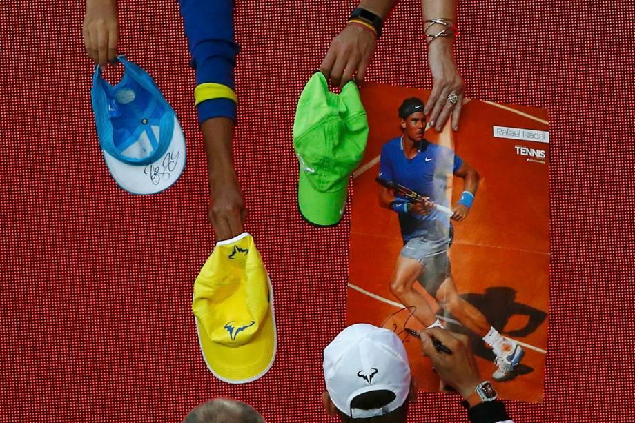 O espanhol Rafael Nadal dá autógrafos após vencer a partida contra o alemão Alexander Zverev, em Melbourne
