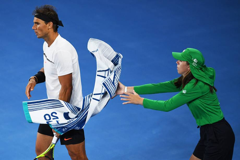 A ball girl catches Spain's Rafael Nadal's towel in his game against Canada's Milos Raonic during their men's singles quarter-final match on day ten of the Australian Open tennis tournament in Melbourne on January 25, 2017.  / AFP PHOTO / Greg Wood / IMAGE RESTRICTED TO EDITORIAL USE - STRICTLY NO COMMERCIAL USE