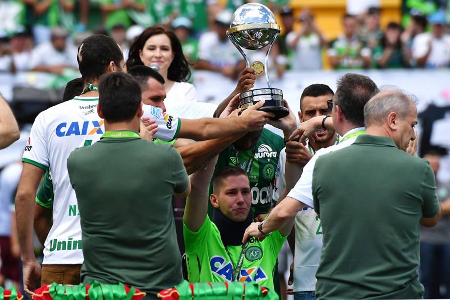 Jackson Follmann, um dos sobreviventes na tragédia em Medellin, levanta a taça da Copa Sul-Americana antes do amistoso entre Chapecoense e Palmeiras, na Arena Condá em Chapecó