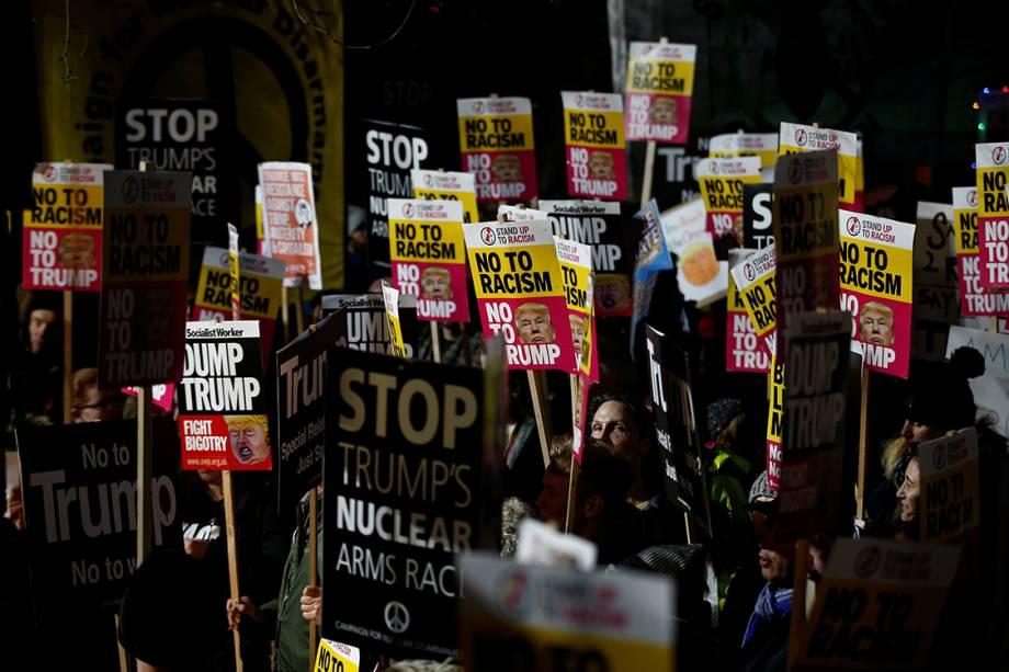 Manifestantes seguram cartazes contra o presidente eleito dos Estados Unidos, Donal Trump, durante sua posse no Capitólio