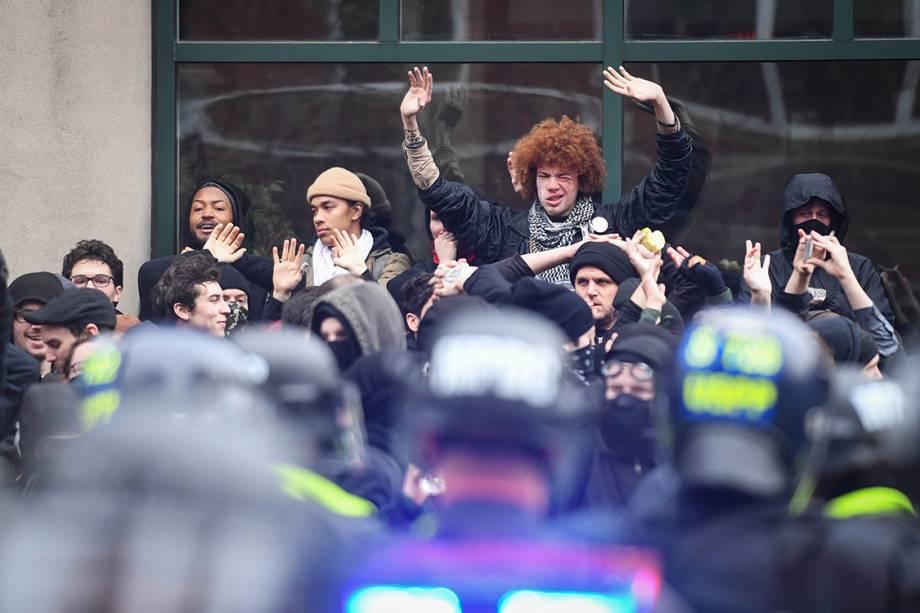 Manifestantes são cercados por policiais durante protesto contra o presidente eleito dos Estads Unidos, Donald Trump
