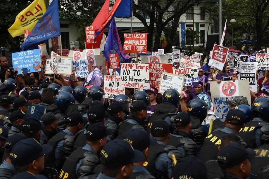 Manifestantes são contidos por uma barreira de policiais em frente à embaixada dos EUA em Manila, nas Filipinas, em protesto no dia da posse de Donald Trump como presidente - 20/01/2017