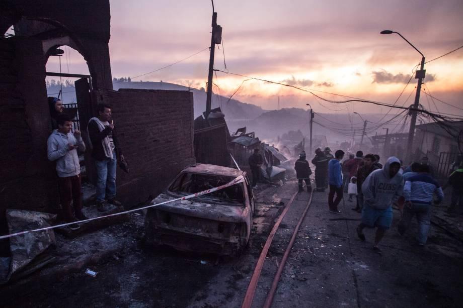 Pessoas trabalham para extinguir as chamas em uma casa em Valparaiso, no Chile