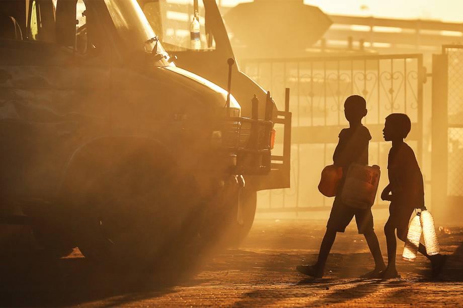 Crianças caminham ao longo de uma estrada para coletar água para suas famílias, em Mumbai, na Índia - 11/01/2017