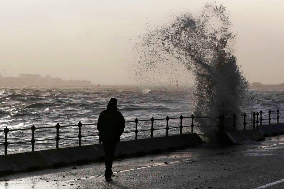 Homem caminha próximo de ondas em New Brighton, no norte da Inglaterra - 11/01/2017