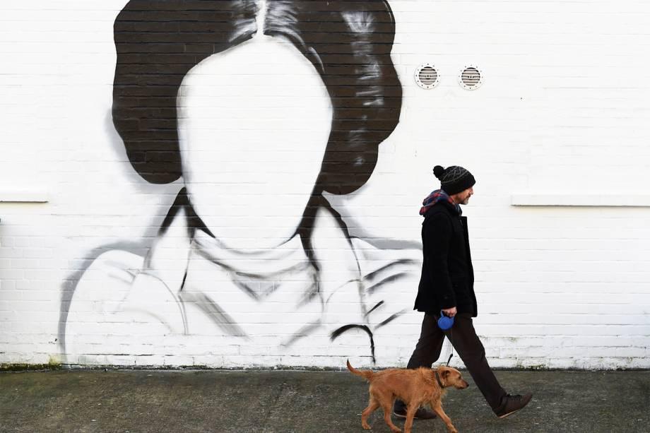 Homem e seu cão caminham próximos de um mural dedicado à Princesa Leia, da franquia 'Star Wars', em Belfast, capital da Irlanda do Norte - 11/01/2017